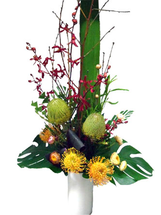 Seasonal native and orchids stunning flower arrangement in a ceramic vase.