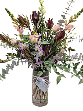 Flower arrangement in a vase including seasonal natives, orchids, snap dragons.